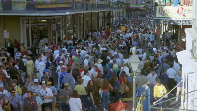 medium angle of crowd in town streets during mardi gras. - new orleans mardi gras stock videos and b-roll footage