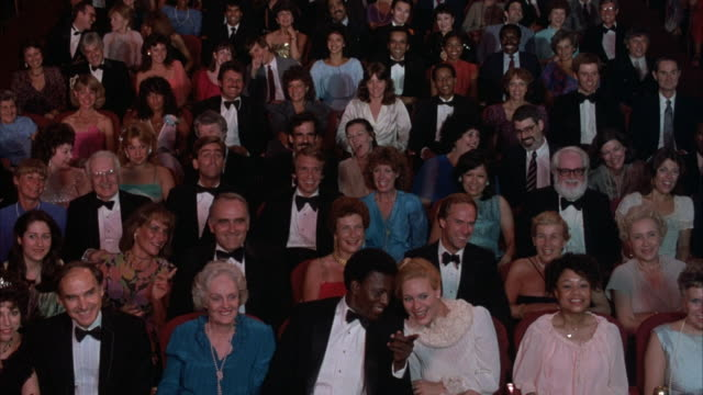 stockvideo's en b-roll-footage met medium angle of audience seated at theater, almost all men wear tuxedos and bow ties, women dressed in evening wear. audience begins clapping and applauding, then stands up for ovation. audience begins to sit at end. - publiek