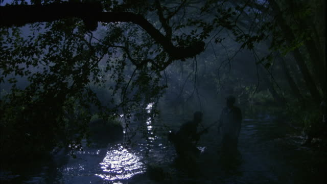 MEDIUM ANGLE OF SOLDIERS WALKING ACROSS RIVER IN FOREST. FOREST IS DARK, SUNLIGHT REFLECTS ON SURFACE OF WATER. LEADER STANDS AS SOLDIERS WALK BY.