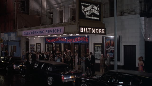 """medium angle of entrance of biltmore theater with signs that read """"manhattan melodies"""" and """"gala opening tonight."""" paparazzi in front of building, take pictures as black limos pull up to theater. camera flashes, people exit other taxis and limos. neg cut. - anno 1984 video stock e b–roll"""