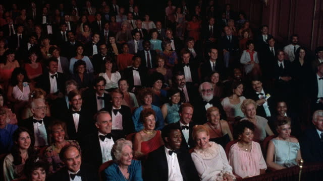 medium angle of audience seated at theater, almost all men wear tuxedos and bow ties, women dressed in evening wear. audience begins clapping and applauding, then stands up for ovation. audience begins to sit at end. - applauding stock videos & royalty-free footage