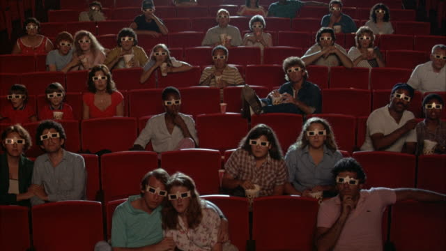 medium angle of audience, people wearing 3-d glasses inside theater. they sit, some people eat popcorn, staring at frame. fish start being thrown at people, they begin cheering, clapping, and applauding. - 映画館点の映像素材/bロール