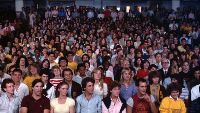 medium angle of audience sitting, could be in gym or school. they begin cheering, clapping, and applauding. - audience stock videos & royalty-free footage