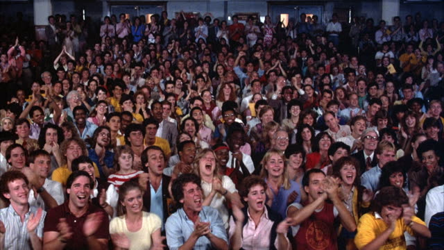 vidéos et rushes de medium angle of audience sitting, could be in gym or school. they are cheering, clapping, and applauding, then stop applauding. - acclamation de joie
