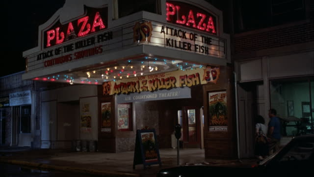 "wide angle of movie theater, marquee reads ""attack of the killer fish,"" neon signs read ""plaza."" other signs read ""attack of the killer fish 3d,"" woman disappears to buy tickets, then walks into entrance with twin boys. - anno 1984 video stock e b–roll"