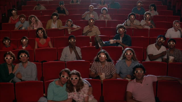 medium angle of audience, people wearing 3-d glasses, in theater, staring at frame. fish start being thrown at people, they begin cheering, clapping, and applauding. neg cut. - 3d glasses stock videos & royalty-free footage