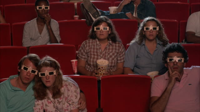 medium angle of audience, people wearing 3-d glasses, in theater, staring at frame. fish start being thrown at people, they begin cheering, clapping, and applauding. - 3d glasses stock videos & royalty-free footage