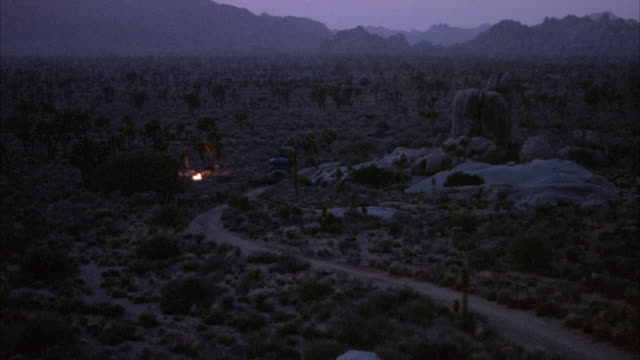 established wide angle of desert with shrubs. campfire burning off centered to left. mountains in background. see shadows of people after campfire dies out. - bonfire stock videos & royalty-free footage