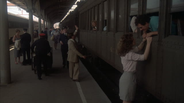 pan left to right of train in station, train begins moving into frame, woman holding onto man in window, saying goodbye. conductor signals for all aboard, people run by to get on train. - saying goodbye stock videos & royalty-free footage