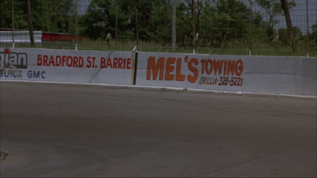 PAN RIGHT TO LEFT. MEDIUM ANGLE OF RACETRACK WALL ADS. SEE 'MEL'S TOWING' AND OTHER CAR ADS. RED RACECAR DRIVES AROUND BEND OF RACETRACK. PANS LEFT TO FOLLOW CAR. CAR RUNS INTO SIDE OF WALL AND KEEPS DRIVING. SEE TWO MEN STANDING NEXT TO TWO CARS ON SIDE