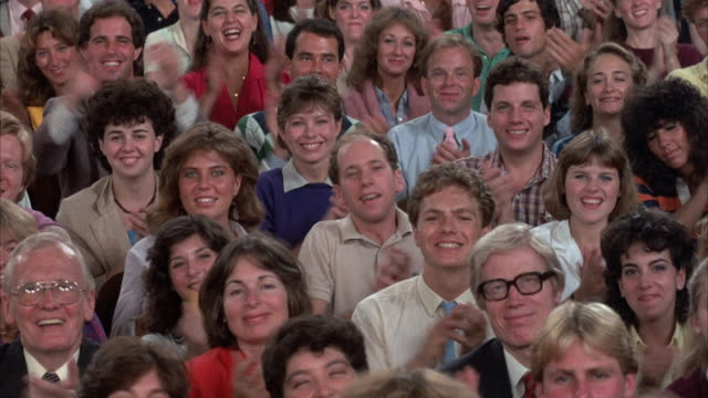 medium angle of audience sitting down. they begin cheering and applauding, then stop at end of shot. could be inside community center, school, or auditorium. - applaudire video stock e b–roll