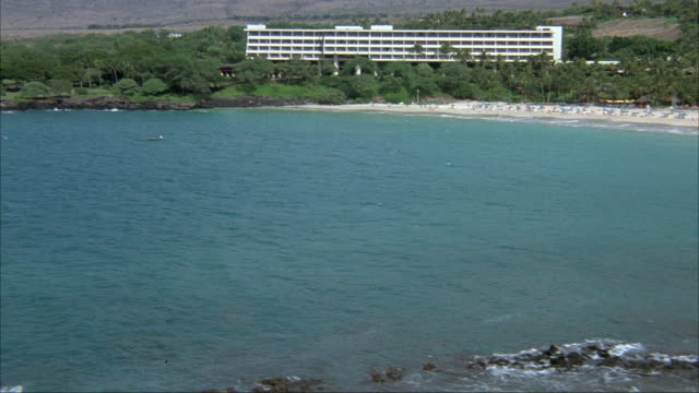 AERIAL. PASSING OVER OCEAN. BEACH RESORT IN BACKGROUND. SEE MOUNTAINS IN DISTANCE.  ACTUAL HOTEL NAME AND LOCATION IS MAUNA KEA BEACH HOTEL, KOHALA COAST ON BIG ISLAND OF HAWAII.