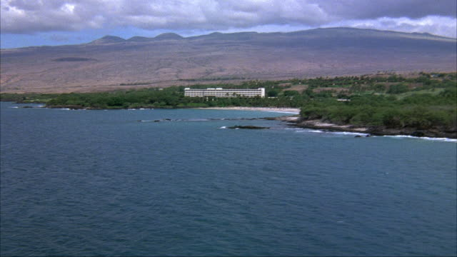 AERIAL. PASSING OVER OCEAN. BEACH RESORT OR HOTEL IN BACKGROUND. SEE MOUNTAINS IN DISTANCE. ACTUAL HOTEL NAME AND LOCATION IS MAUNA KEA BEACH HOTEL, KOHALA COAST ON BIG ISLAND OF HAWAII.