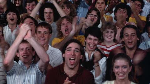 medium angle of audience sitting and cheering by clapping and shouting. - applådera bildbanksvideor och videomaterial från bakom kulisserna