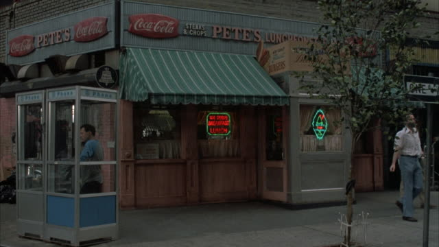 "vídeos de stock, filmes e b-roll de medium angle of ""pete's luncheon"". see people walking down sidewalk and see person talking on phone inside phone booth. see neon signs in window, awnings and ""coca cola"" signs. neg cut. - cabine de telefone público telefone público"