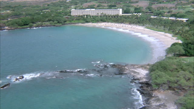 AERIAL OF OCEAN AND BEACH WITH LARGE WHITE BUILDING POSSIBLY HOTEL IN BACKGROUND. WAVES CRASH ON REEF IN BOTTOM OF SHOT. POSSIBLY PEOPLE LOUNGING ON BEACH IN BACKGROUND. TREE LINE SEPARATES BEACH FROM BUILDING. FOREST SURROUNDS SHORELINE.  ACTUAL HOTEL NA