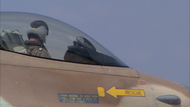 MEDIUM ANGLE OF A CAMOUFLAGE F-16 FIGHTER JET MOVING DOWN RUNWAY. POV LOOKING AT TAIL. MIDDLE EAST.
