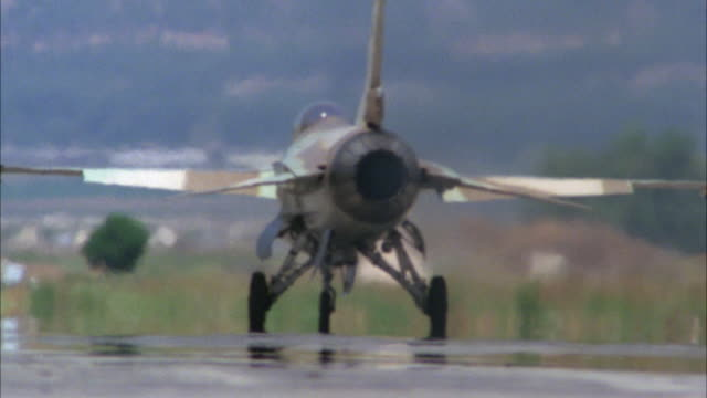 MEDIUM ANGLE OF A CAMOUFLAGE F-16 FIGHTER JET WAITING ON RUNWAY. SEE REAR ENGINE OPEN UP. POV LOOKING AT TAIL. MIDDLE EAST.