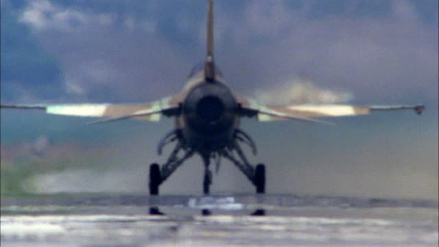 tracking shot of three camouflage f-16 fighter jets taking off from runway. follows third jet into sky. see rear engines glowing. neg cut. middle east. - fighter stock videos & royalty-free footage