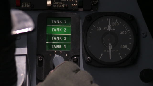 close angle of gloved hand steering off screen yoke while moving dial to change to various fuel tanks. see panel light up for each tank. see fuel meter at side. see light shining on panel as pilot maneuvers plane. neg cut. - 計測器点の映像素材/bロール