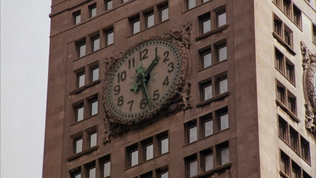 MEDIUM ANGLE OF GIANT CLOCKS ON SIDES OF OFFICE BUILDING. TIME IS ONE TWENTY-SEVEN IN THE AFTERNOON.
