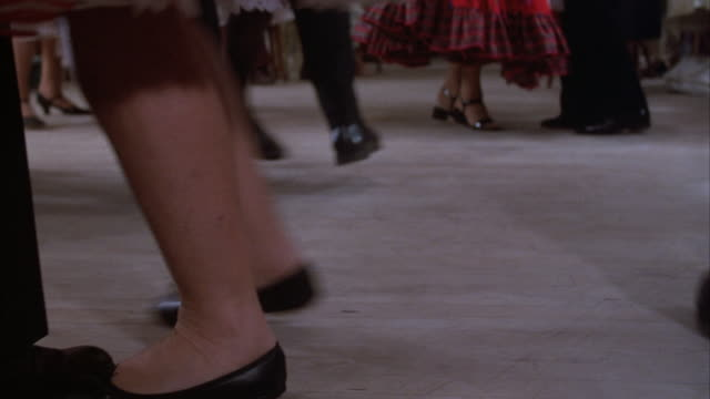 medium angle of feet of men and women dancing. see men wearing black pants and see women wearing spanish style full skirts. - anno 1984 video stock e b–roll