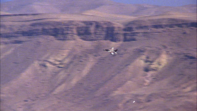 TRACKING SHOT OF A CAMOUFLAGE F-16 JET FIGHTER FLYING OVER DESERT BASIN AREA BORDERED BY MOUNTAINS. MIDDLE EAST.
