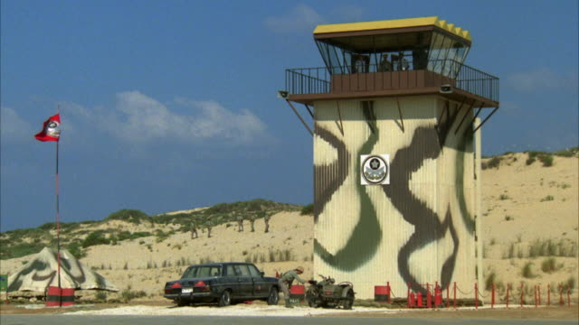 MEDIUM ANGLE OF A MILITARY CONTROL TOWER WITH A RED FLAG ON SIDE AND CAR PARKED IN FRONT. SEE MAN BEGIN TO RUN AWAY WHEN MISSILE HITS AREA IN FRONT OF CONTROL TOWER AND CAUSES AND EXPLOSION WITH A BURST OF FIRE. SEE AREA FILLED WITH BLACK SMOKE. EXPLOSION