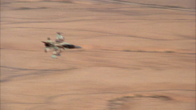 TRACKING SHOT OF A CAMOUFLAGE F-16 FIGHTER JET FLYING OVER DESERT AREA. SEE JET DESCEND LOW TO GROUND, ASCEND BACK INTO SKY AND BANK RIGHT. MIDDLE EAST.