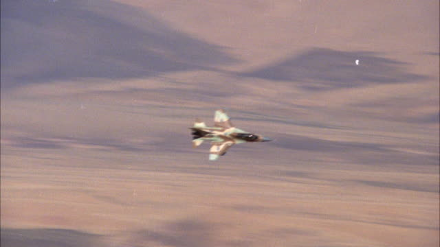 TRACKING SHOT OF A CAMOUFLAGE F-16 FIGHTER JET FLYING OVER DESERT AREA. SEE JET DESCEND LOW TO GROUND AND ASCEND BACK INTO SKY. MIDDLE EAST.