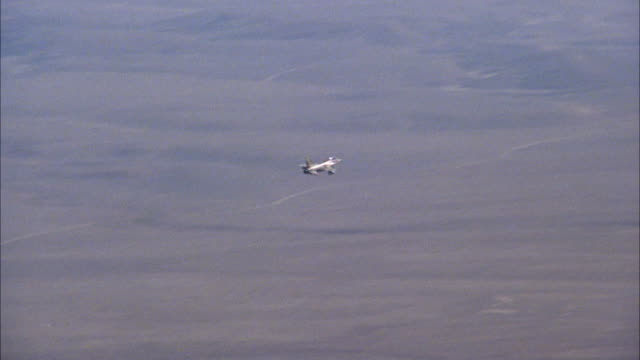 TRACKING SHOT OF A CAMOUFLAGE F-16 FIGHTER JET FLYING OVER DESERT AREA. MIDDLE EAST.