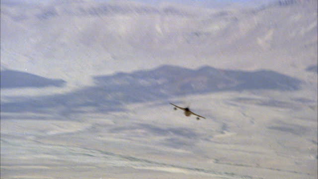 TRACKING SHOT OF A CAMOUFLAGE F-16 FIGHTER JET QUICKLY DESCENDING TOWARDS GROUND. THEN SEE JET BEGIN TO ASCEND. MIDDLE EAST.