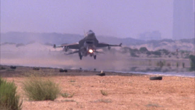 TRACKING SHOT OF A CAMOUFLAGE F-16 FIGHTER JET APPROACH AND LAND ON RUNWAY. CUTS TO VIEW OF TAIL AS IT MOVES PAST THE CAMOUFLAGE CONTROL TOWER. SEE DESERT AREA IN BACKGROUND. MIDDLE EAST.