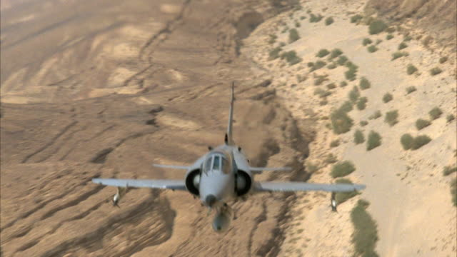 TRACKING SHOT OF A CAMOUFLAGE F-16 FIGHTER JET FLYING OVER DESERT AREA WITH SPARSE VEGETATION. SEE JET APPROACHING OVER TOP OF MOUNTAINS AND DRY RIVER AREA. MIDDLE EAST.