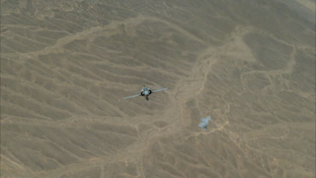 TRACKING SHOT OF TWO CAMOUFLAGE F-16 FIGHTER JETS FLYING. SEE JETS BANKING LEFT AND RIGHT. SEE LAND BELOW. MIDDLE EAST.