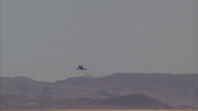 TRACKING SHOT OF A CAMOUFLAGE F-16 FIGHTER JET TAKING OFF FROM RUNWAY. SEE JET FLY INTO DISTANCE, BANK RIGHT AND MAKE A CIRCLE AROUND. SEE JET FLY OFF SCREEN AS ANOTHER JET FLIES PAST. CUTS BACK TO FIRST JET FLYING BACK OVER RUNWAY UNTIL OFF SCREEN. MIDDL