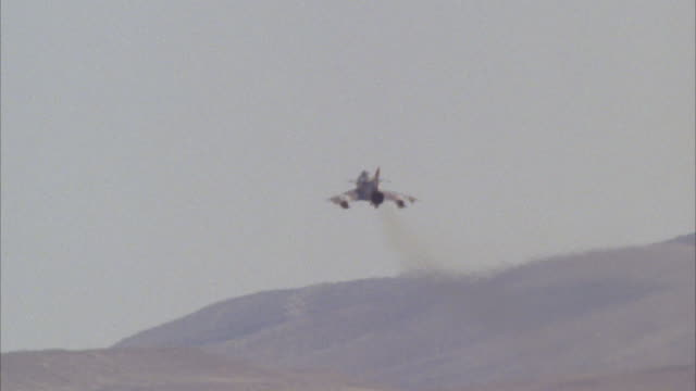 TRACKING SHOT OF A CAMOUFLAGE F-16 FIGHTER JET FLYING AWAY INTO DISTANCE UNTIL OFF SCREEN. SEE MOUNTAINS IN BACKGROUND. MIDDLE EAST.