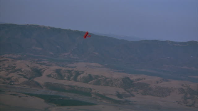 medium aerial of red biplane or airplane in distance flying across hills toward front. high angle down of bare hills as top of biplane passes by. - biplane stock videos & royalty-free footage