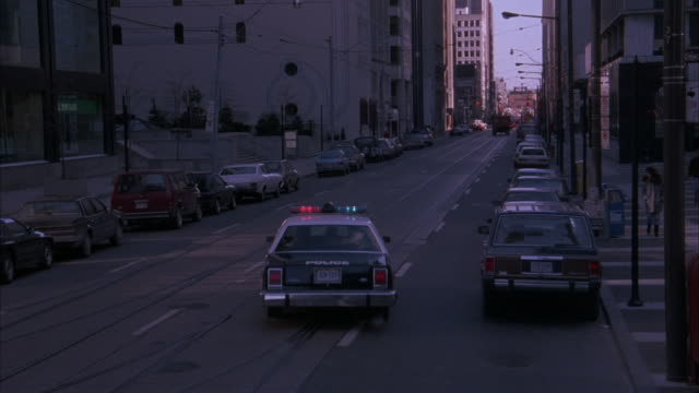 stockvideo's en b-roll-footage met medium angle of city street in downtown toronto. police car turns left on corner, followed by four cars. neg. cut. - ontario canada