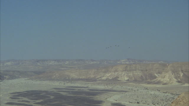 TRACKING SHOT OF SIX CAMOUFLAGE F-16 FIGHTER JET FLYING IN A 'V' FORMATION. SEE JETS APPROACHING AND THEN FLY OFF SCREEN. SEE MOUNTAINS IN BACKGROUND. MIDDLE EAST.