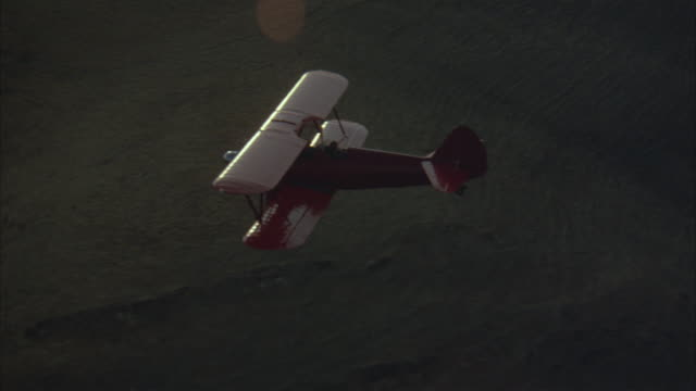 medium aerial tracking shot of red biplane or airplane flying across hills from right to left. sun rays reflect on lens. - biplane stock videos & royalty-free footage