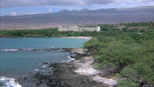 WIDE ANGLE AERIAL OF RESORT BY BEACH. SEE BODY OF WATER OR OCEAN ON LEFT FOREGROUND, WHITE BUILDING OR HOTEL SURROUNDED BY TREES. HILL AND MOUNTAINS IN BACKGROUND, SUNBATHERS ON BEACH. ACTUAL HOTEL NAME AND LOCATION IS MAUNA KEA BEACH HOTEL, KOHALA COAST
