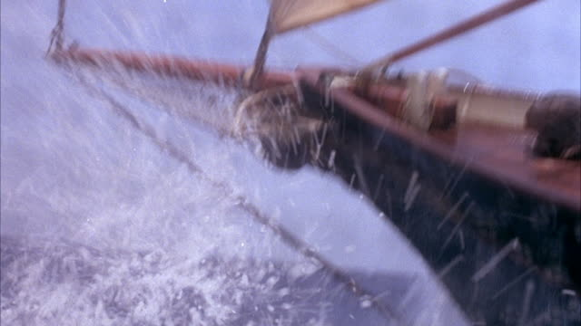 medium angle of bow of sailboat as it sails over choppy water. see deck of boat at end. - schiff stock-videos und b-roll-filmmaterial