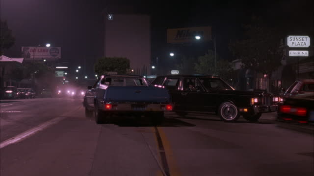 MEDIUM ANGLE FROM MIDDLE OF STREET WITH TRAFFIC ON SIDES OF SUNSET STRIP, STRAIGHT FRONT ANGLE OF STREET. BILLBOARDS OF 'JAY LENO' AND NIKON IN DISTANCE. 'SUNSET PLAZA' SIGN ON RIGHT. BLACK LINCOLN CROSSES OVER CENTER LINE TO RIGHT CRASHES RED CADILLAC, B