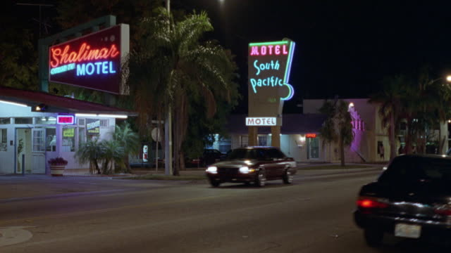 "MEDIUM ANGLE OF CARS DRIVING DOWN CITY STREET. SEE ""MOTEL SOUTH PACIFIC"" AND ""SHALIMAR MOTEL"". NEG CUT."