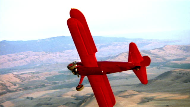 medium aerial of red biplane or airplane in front. biplane turns, tilts to its right and leaves shot to right. bare hills in background. dirt on film. - biplane stock videos & royalty-free footage