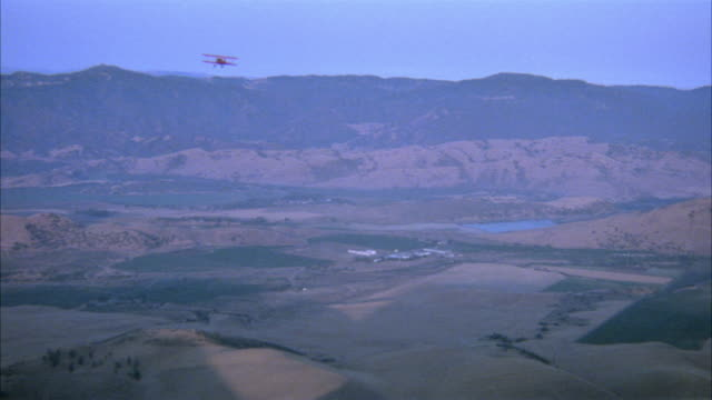 wide angle aerial red biplane or airplane flying toward hills in distance and flying back toward front. high angle down of bare hills as top of biplane passes by. dirt on film. - 複葉機点の映像素材/bロール