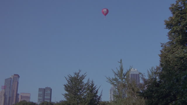 wide angle of red hot air balloon flying. new york city skyline in background. - 1994 stock videos and b-roll footage