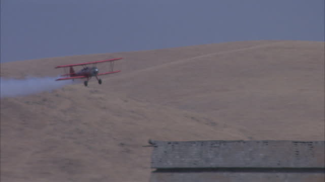 medium angle aerial tracking shot of red biplane or airplane. biplane lowers elevation across hills in desert, touches ground twice next to barn where cows run to right. cowboy on horse appears from left, waves and biplane gets back in air. - scheune stock-videos und b-roll-filmmaterial