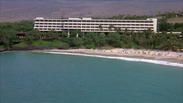 WIDE ANGLE AERIAL OF RESORT BY BEACH. SEE BODY OF WATER OR OCEAN IN FOREGROUND, WHITE BUILDING OR HOTEL SURROUNDED BY TREES. HILL AND MOUNTAINS IN BACKGROUND, SUNBATHERS ON BEACH. ACTUAL HOTEL NAME AND LOCATION IS MAUNA KEA BEACH HOTEL, KOHALA COAST ON BI